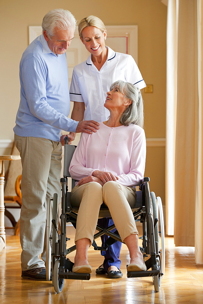 Smiling senior man and home caregiver talking to senior woman in wheelchair