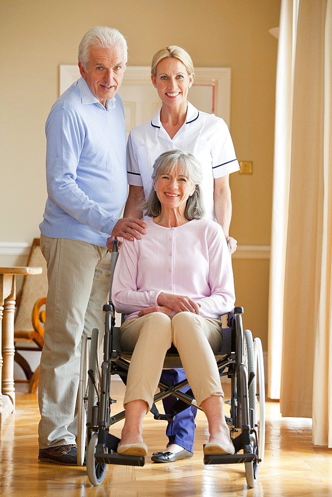Portrait of smiling home caregiver and senior man with senior woman in wheelchair
