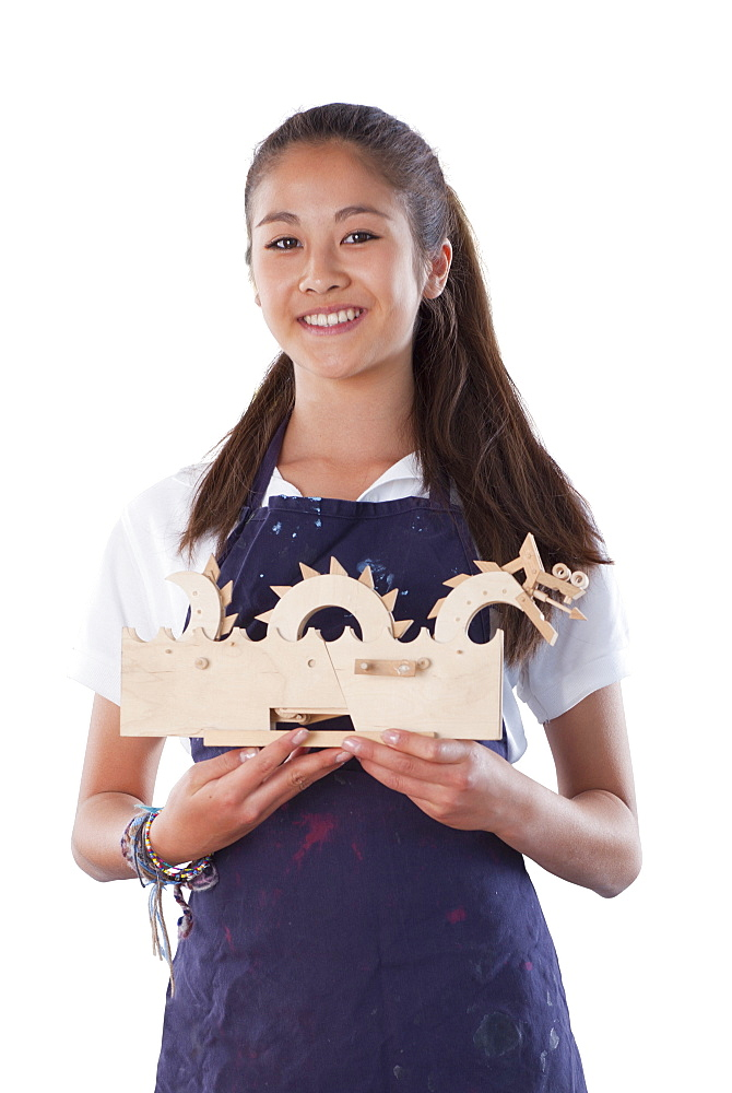Cut Out Of Female Pupil Holding Wooden Model In Design Technology Class