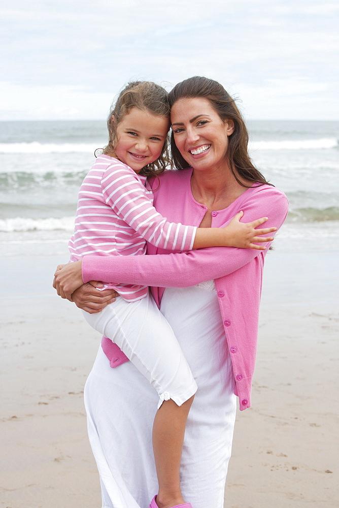 Mother And Daughter Walking Along Summer Beach
