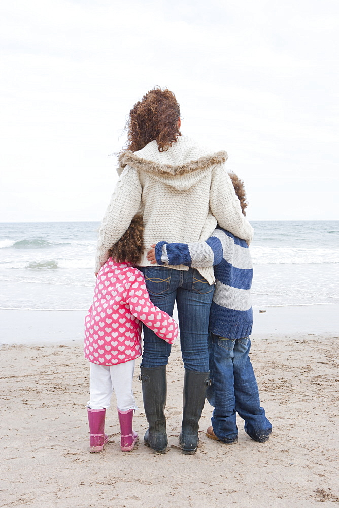Rear View Of Mother Hugging Children On Winter Beach