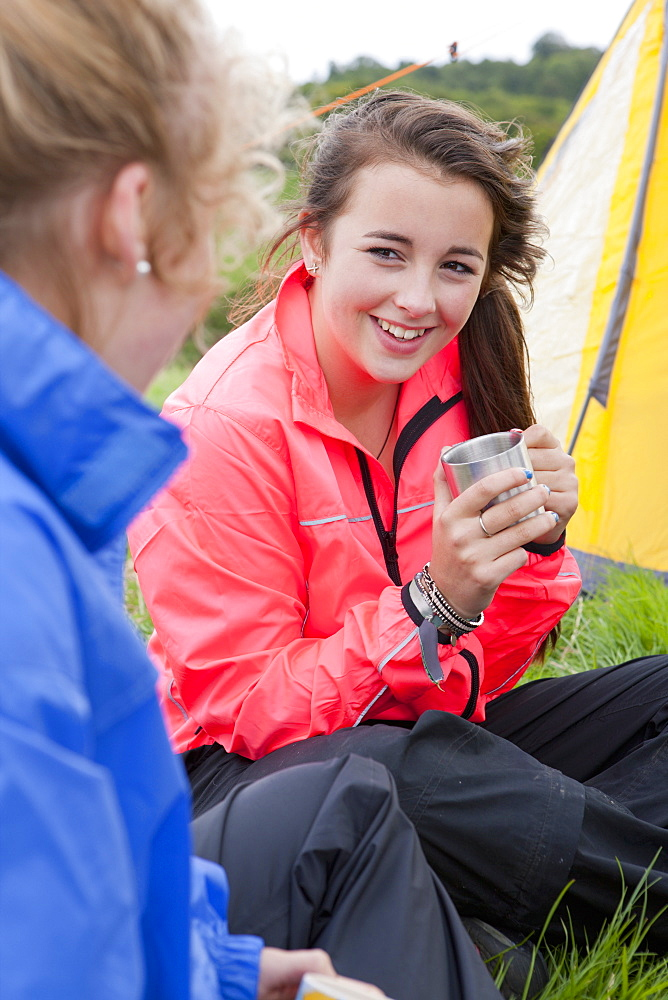 Close up of smiling girls drinking tea next to tent