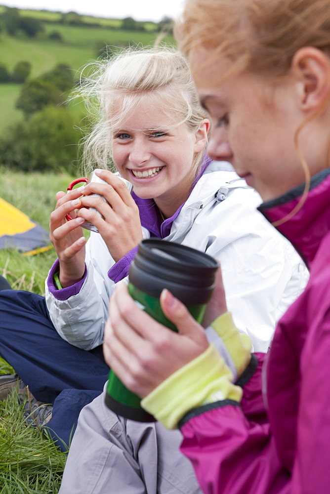 Close up portrait of smiling girls drinking tea in grass