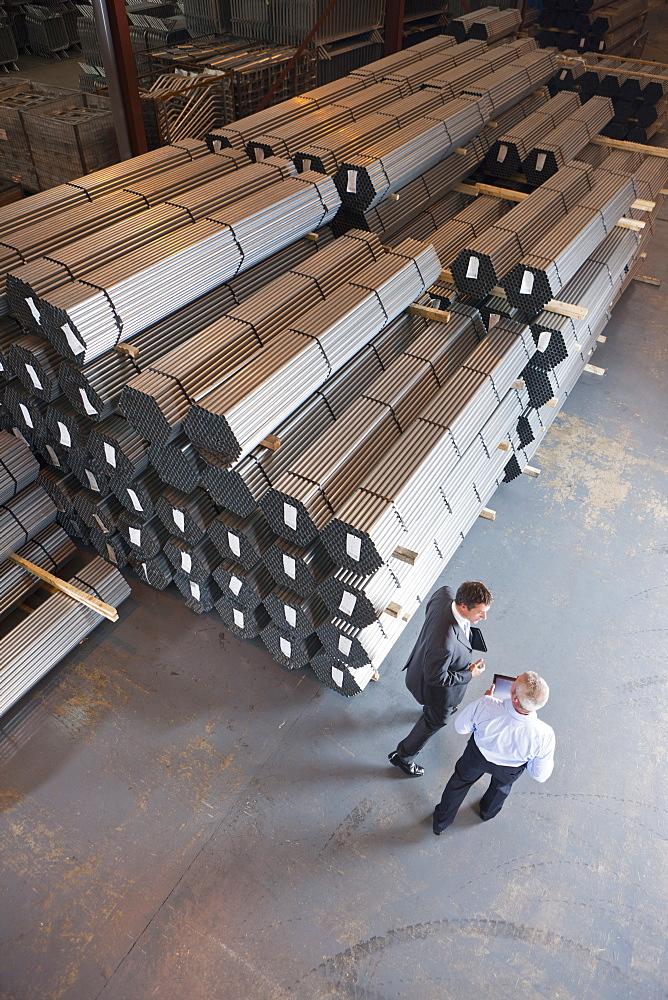 Businessmen talking near steel tubing in warehouse