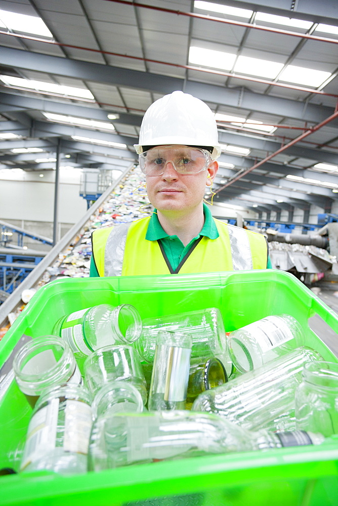 Portrait of worker holding bin with glass bottles in recycling plant