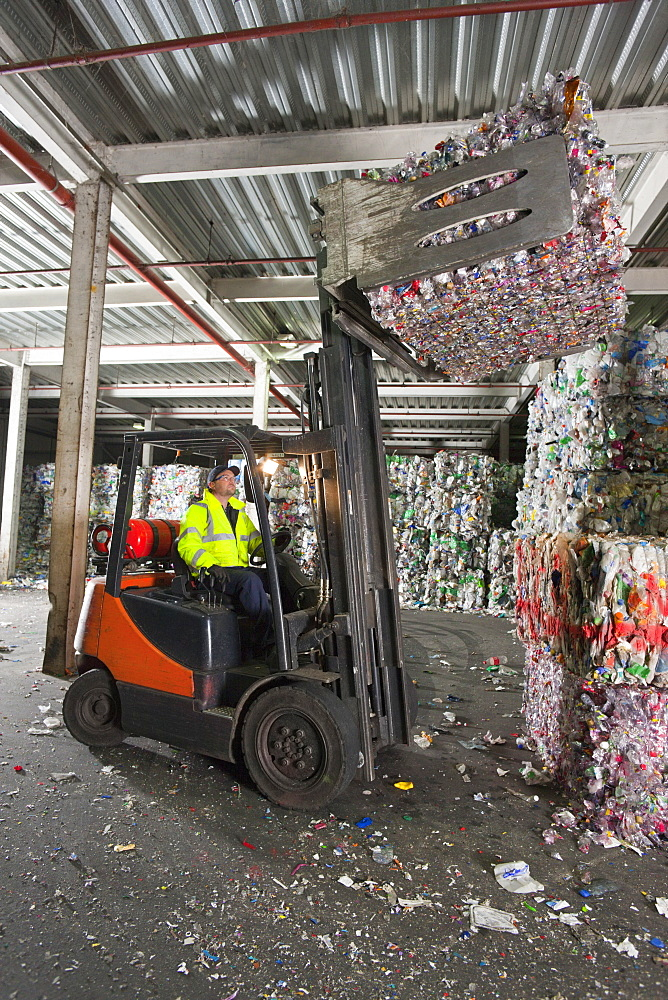 Forklift operator lifting bale of recycled plastic in recycling plant