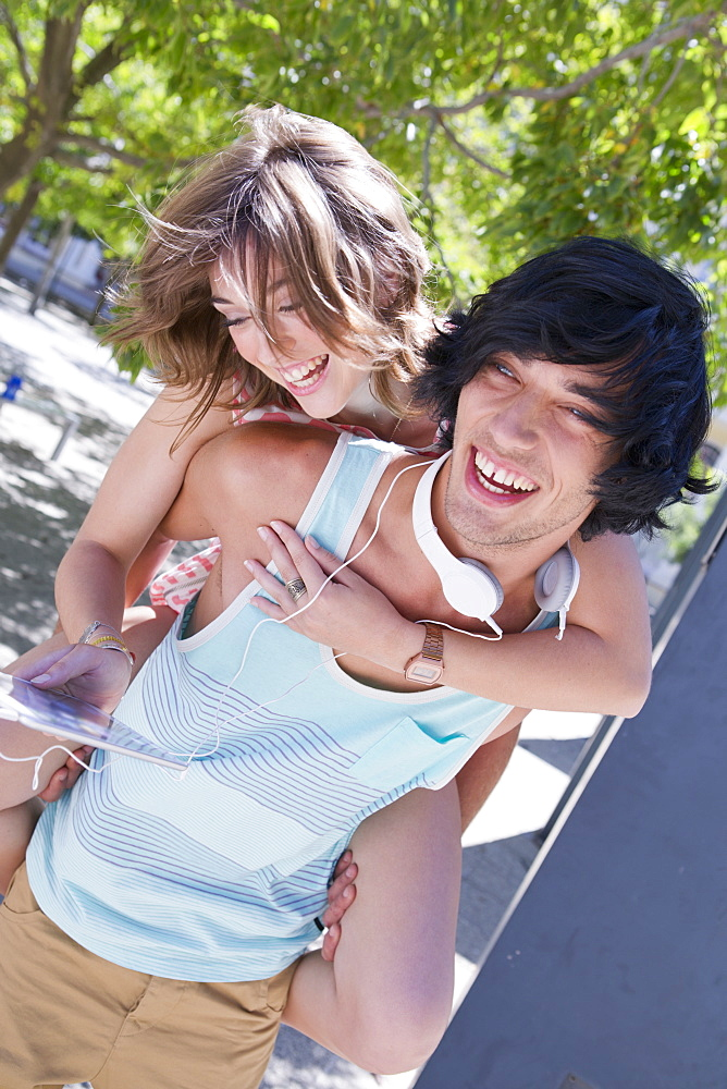 Smiling couple piggybacking and listening to music on digital tablet