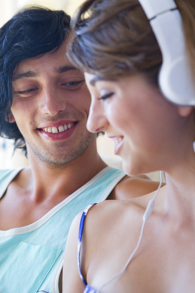 Close up of smiling young couple wearing headphones and listening to music - 786-9008