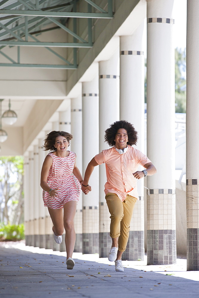 Young couple holding hands and running along outdoor corridor