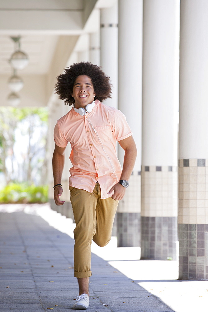 Portrait of smiling young man running along outdoor corridor