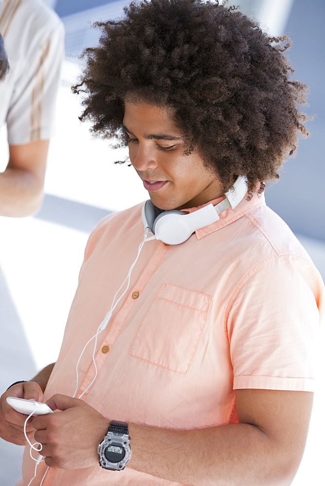 Close up of young man with headphones text messaging on cell phone