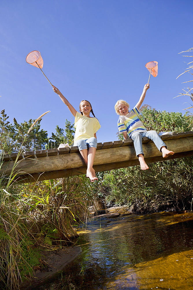 Portrait of smiling boy and girl hold fishing nets overhead on footbridge over stream