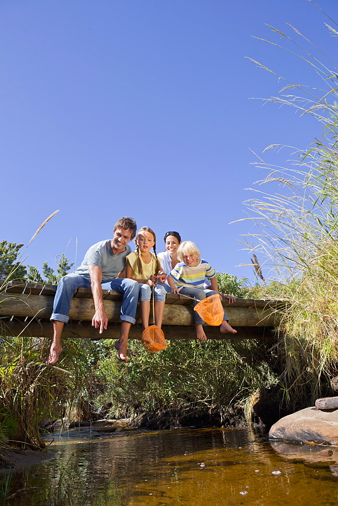 Family with fishing nets sitting on footbridge and looking down at stream