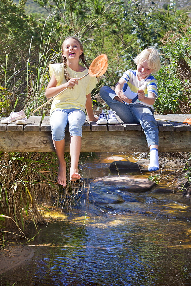 Happy boy and girl with fishing net removing shoes and socks on footbridge over stream