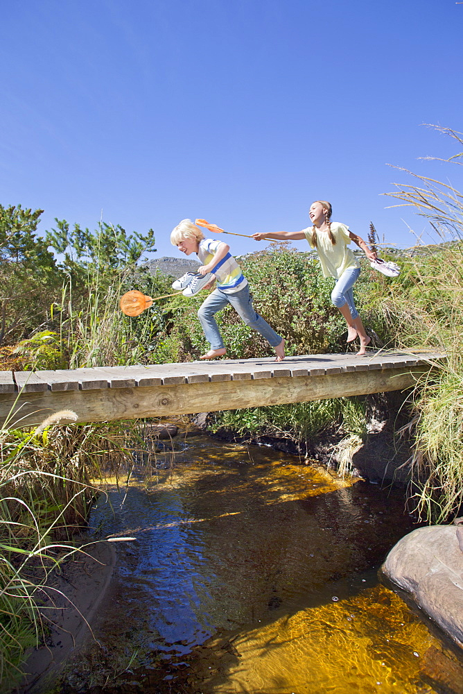 Girl chasing boy with fishing net on footbridge over stream