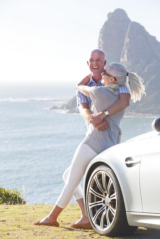 Enthusiastic couple hugging outside car near ocean