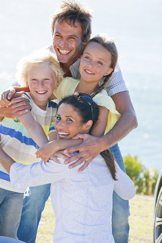 Portrait of enthusiastic family hugging