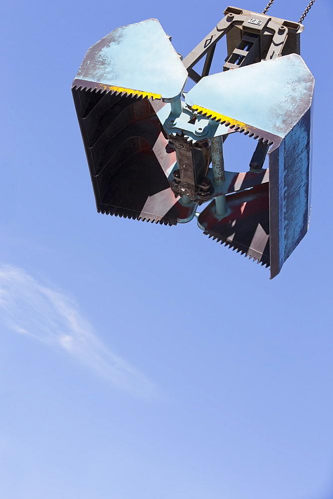 Grab bucket against blue sky