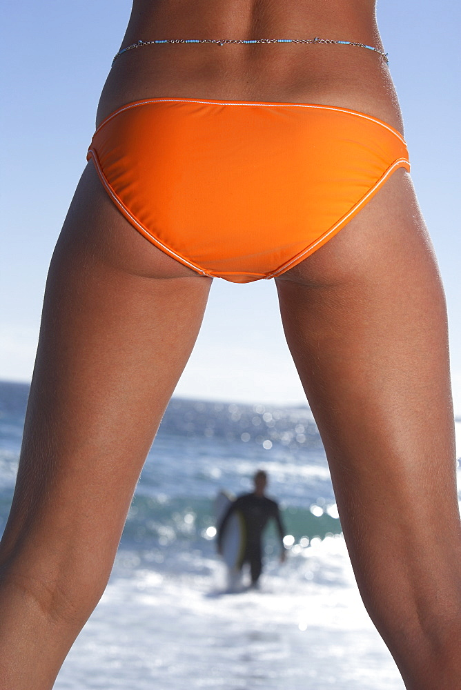 Young woman in orange bikini watching surfer leaving sea, rear view, mid-section, close-up