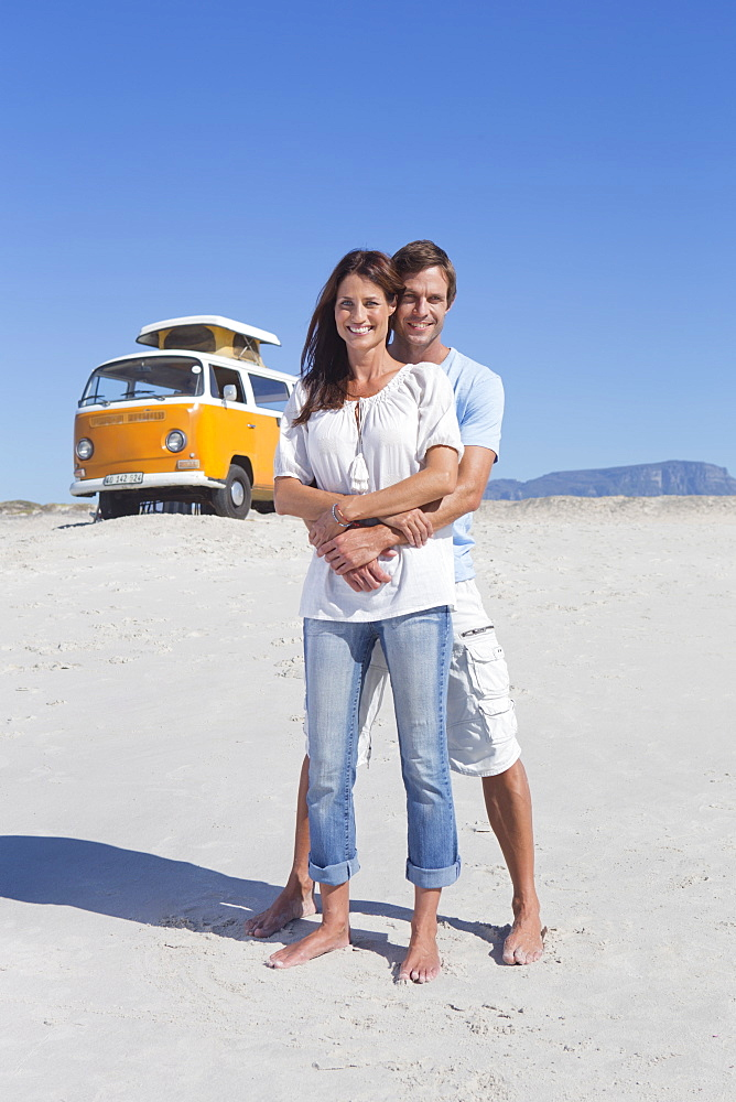Portrait of happy couple hugging on beach with van in background
