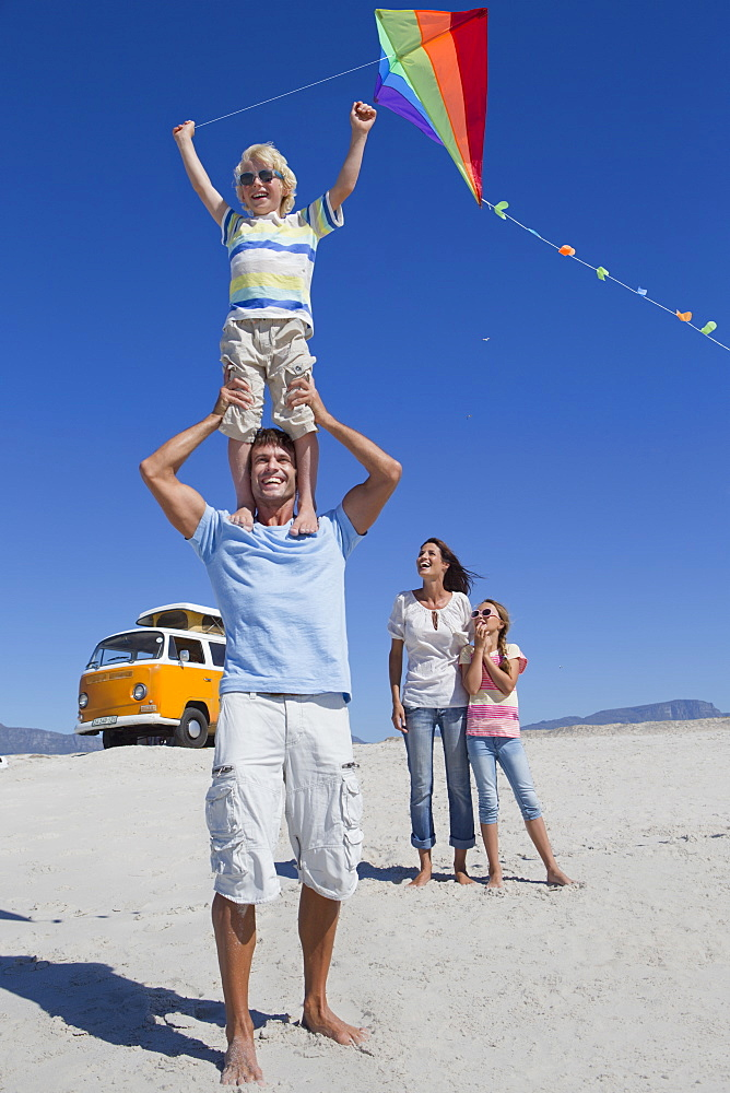 Happy family flying kite on sunny beach with van in background