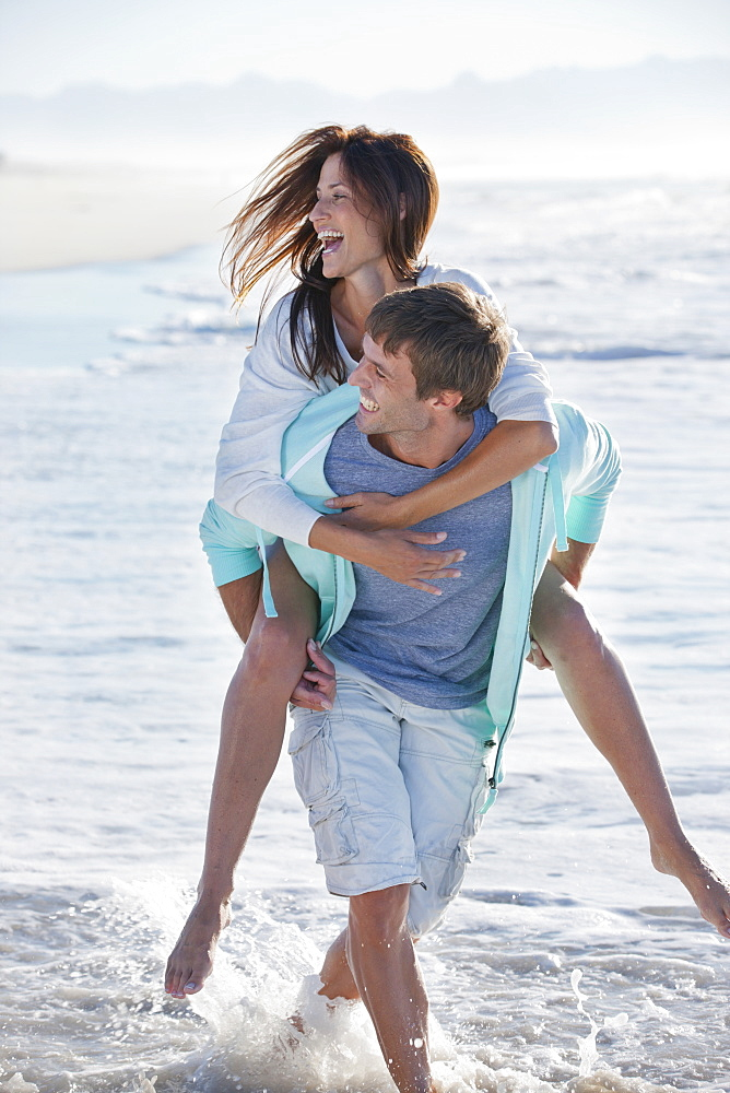 Man piggybacking enthusiastic woman on sunny beach