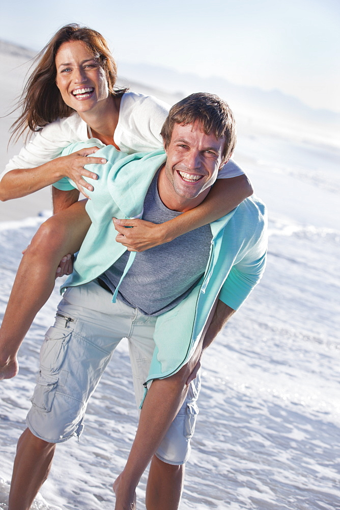 Portrait of smiling man piggybacking woman on sunny beach
