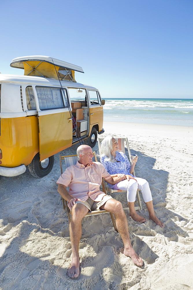 Happy senior couple sitting in lounge chairs on sunny beach near van