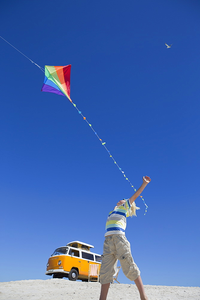 Boy flying kite on sunny beach with van in background