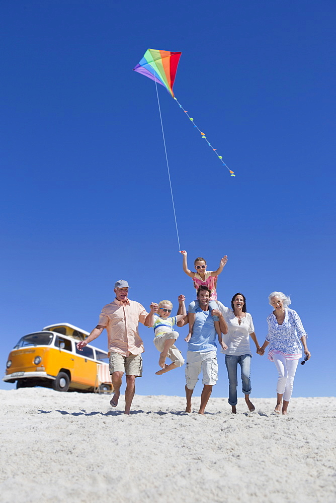 Happy multi-generation family with kite walking on sunny beach with van in background