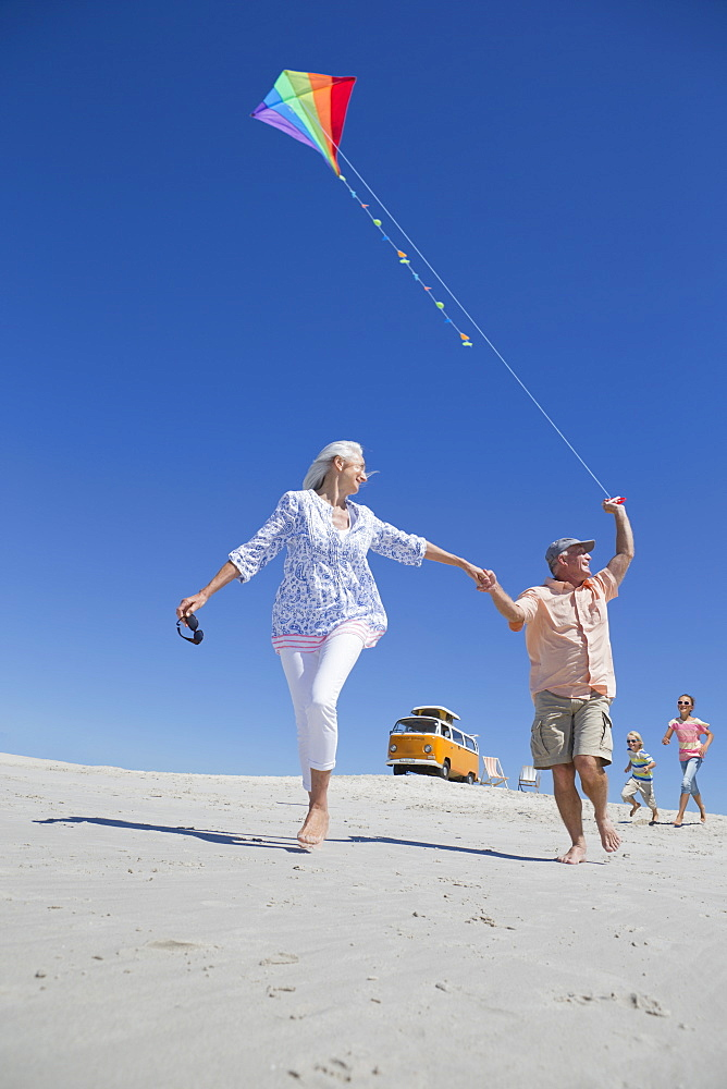 Grandparents and grandchildren with kite running on sunny beach with van in background