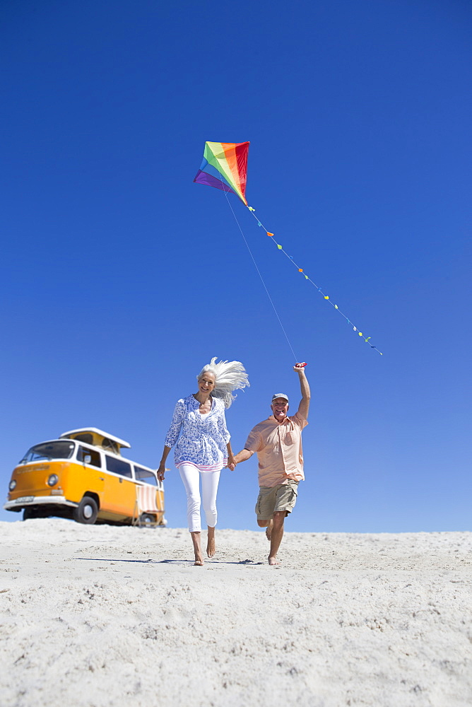 Happy senior couple running with kite on sunny beach with van in background