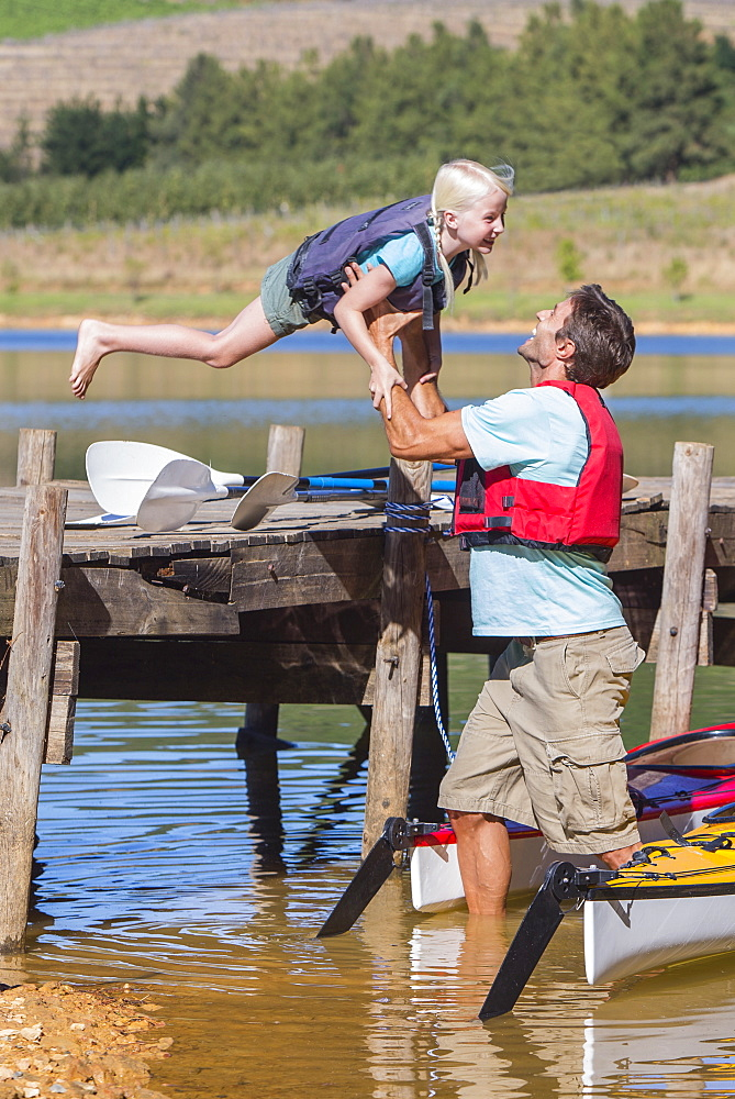 Daughter jumping off dock into father