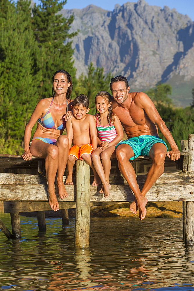 Portrait of smiling family sitting on dock over lake