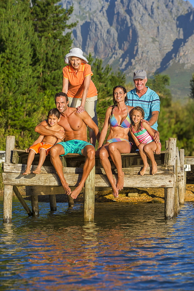 Portrait of smiling multi-generation family on dock over lake