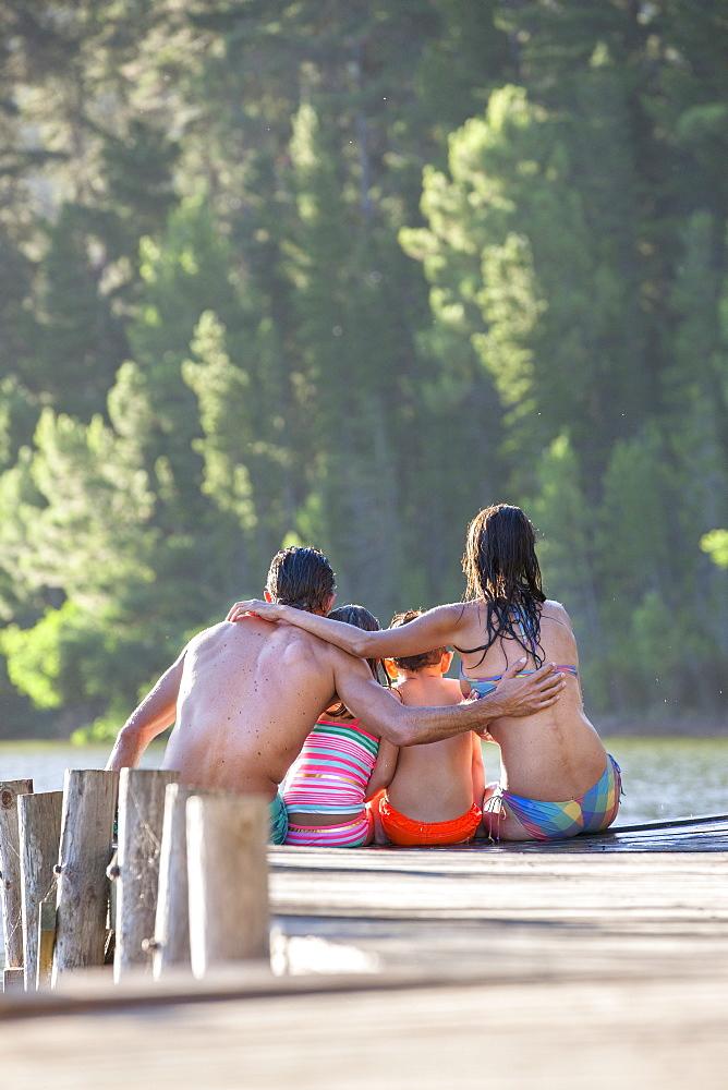 Family hugging at the edge of dock at lake