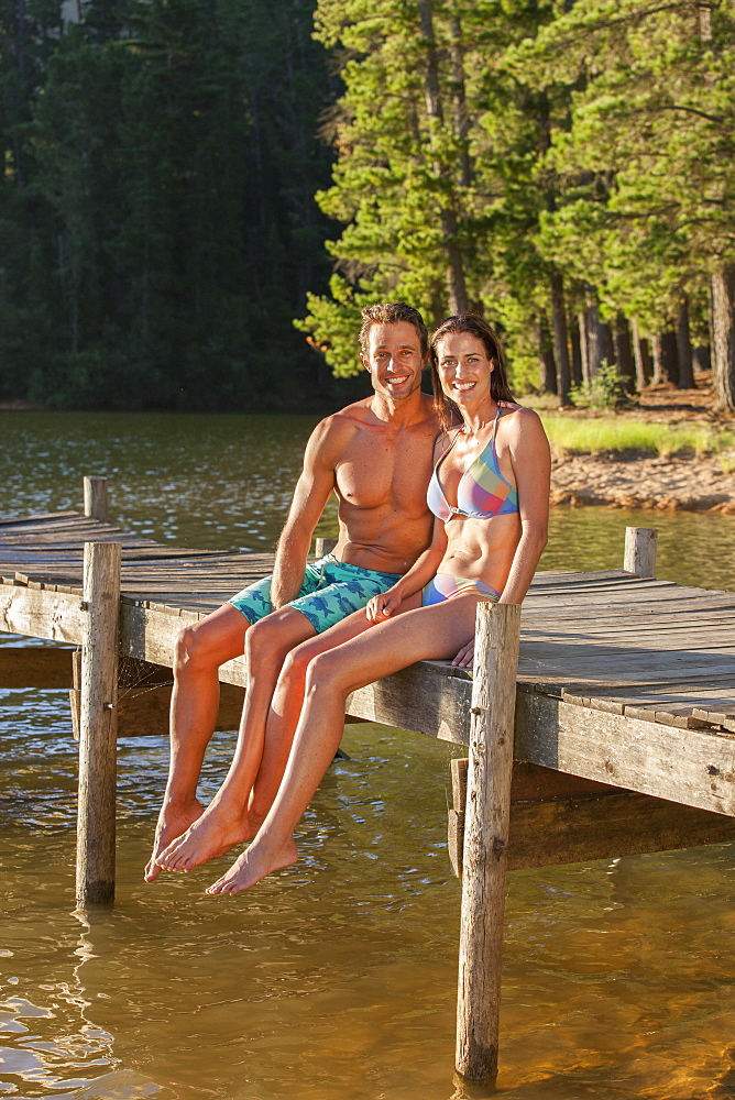 Portrait of happy couple sitting at the edge of dock over lake