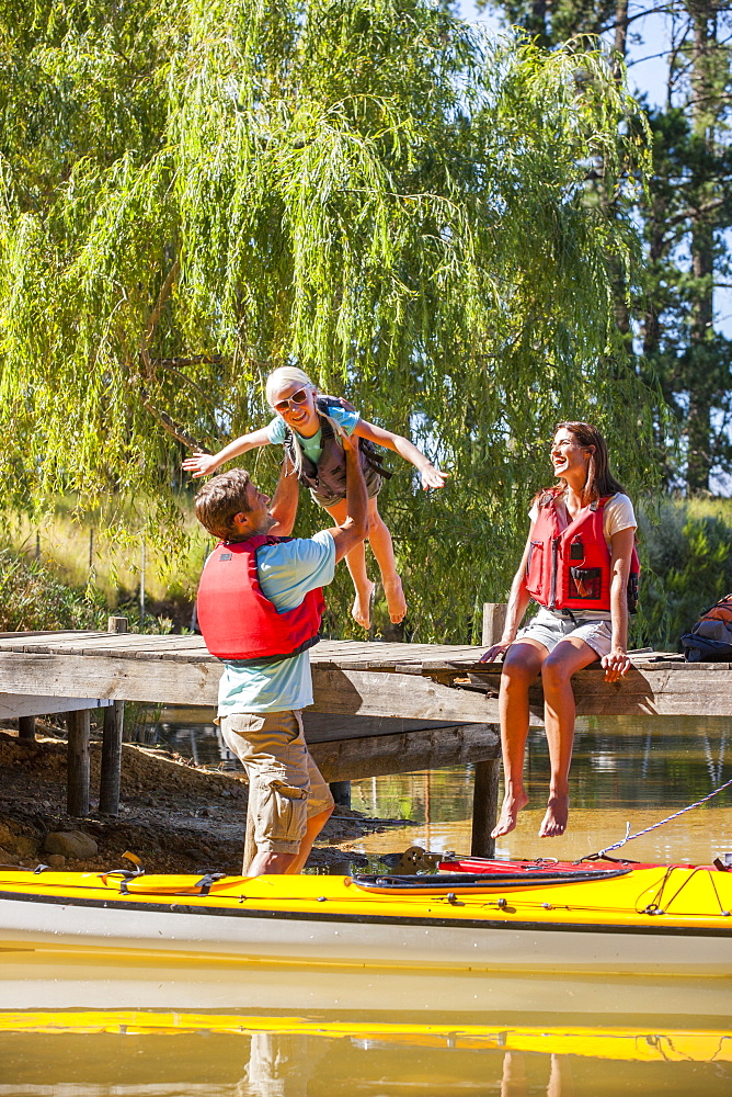 Father lifting daughter from dock into kayak on lake