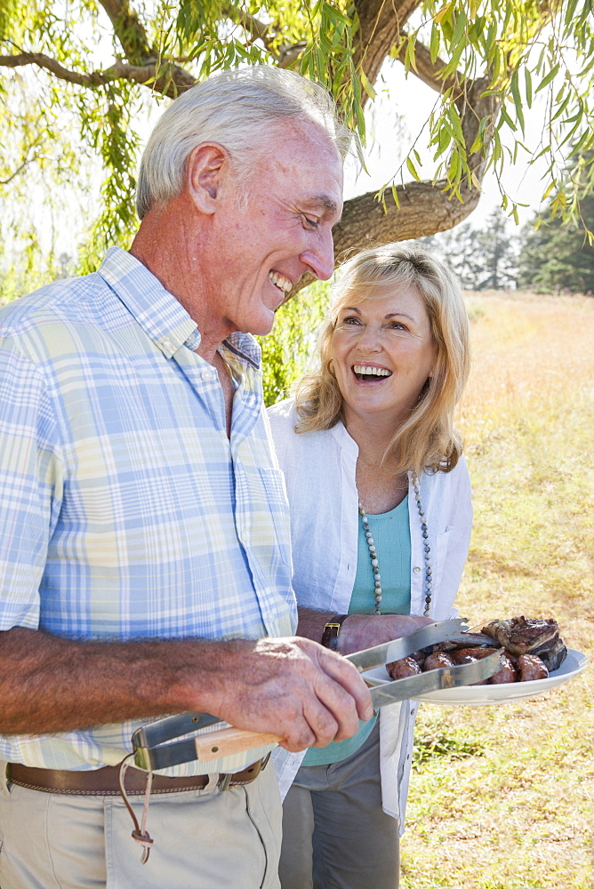 Senior Couple Enjoying Barbeque In Countryside
