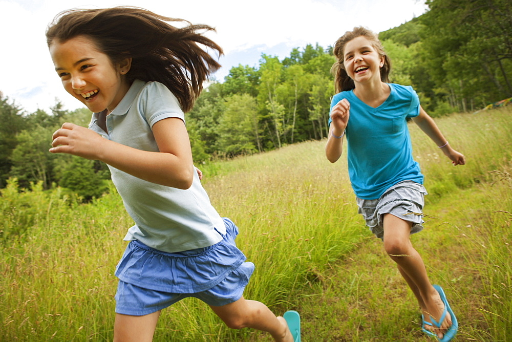 Two children, girls running and playing chase, laughing in the fresh air, New York state, USA