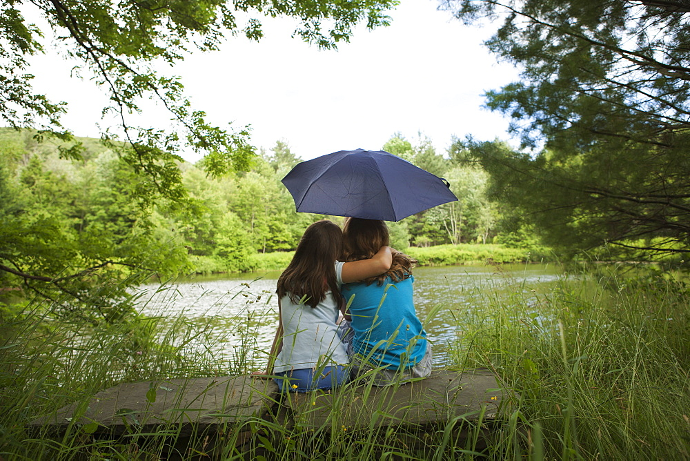 Two children, girls sitting together by a lake, under an umbrella, New York state, USA