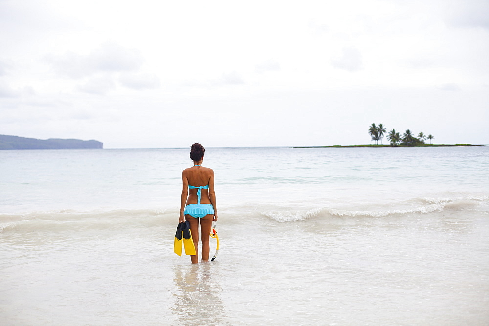 A young woman in shallow water with snorkelling gear on Samana Peninsula in the Dominican Republic, Samana Peninsula, Dominican Republic.