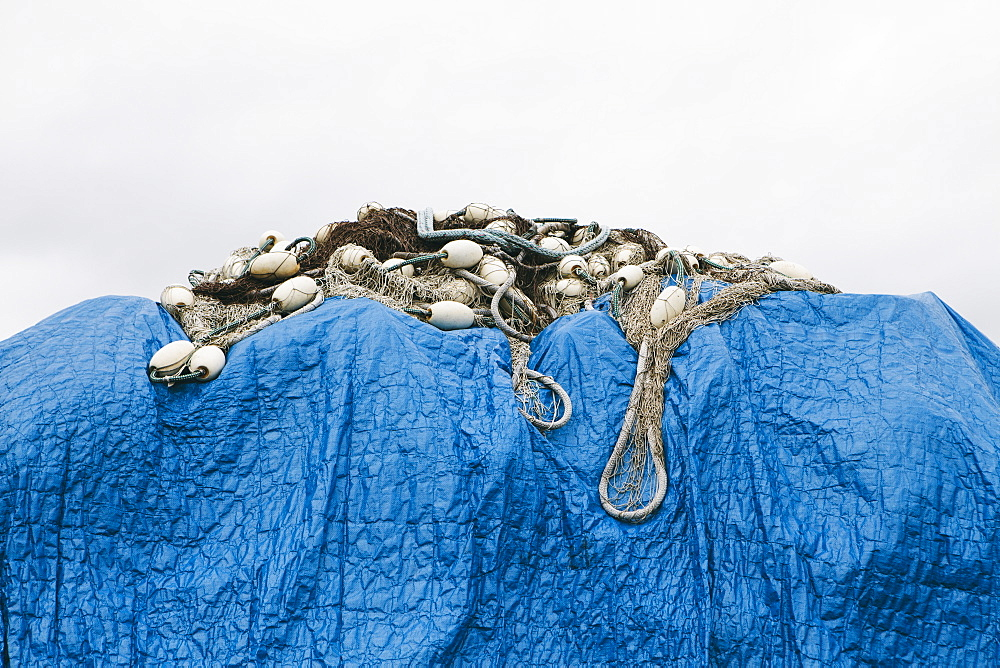 A blue tarpaulin covering stacked commercial fishing nets on the dockside at Fisherman's Wharf, Seattle, Seattle, Washington, USA