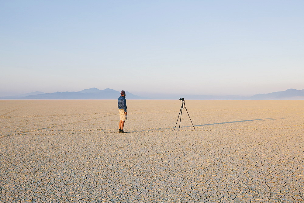 Man with camera and tripod on the flat saltpan or playa of Black Rock desert, Nevada, Black Rock Desert, Nevada, USA
