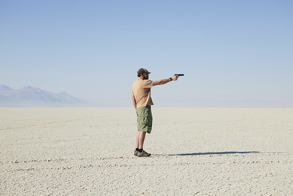 Man aiming hand gun, standing in vast, barren desert, Black Rock Desert, Nevada, USA