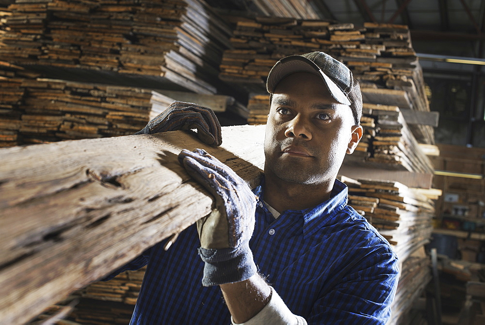 A heap of recycled reclaimed timber planks of wood. Environmentally responsible reclamation in a timber yard. A man carrying a large plank of splintered rough wood, Pine Plains, New York, USA