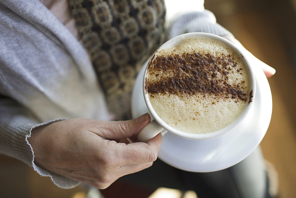 A person holding a full cup of frothy cappuccino coffee in a white china cup. Chocolate powder sprinkled in a pattern on the top. Coffee shop, Kingston, New York, USA