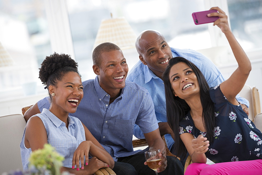 A group of people gathering together for a party or an office event. A woman taking a selfie of the group with a pink smart phone.