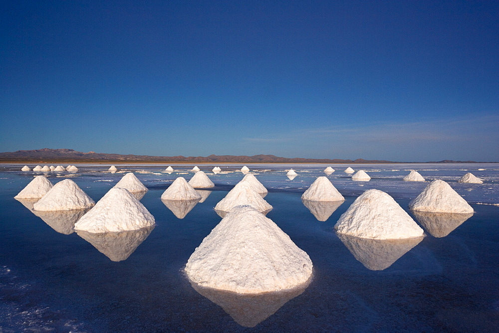Piles of salt dry in the arid atmosphere of Bolivia's Salar de Uyuni, Salar de Uyuni, Bolivia