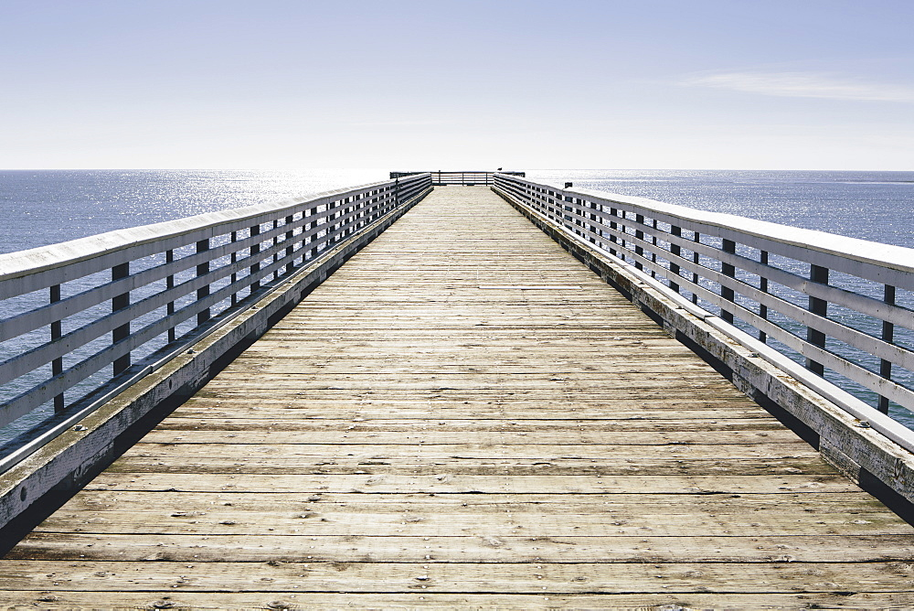 A long pier with railings extending out over the Pacific Ocean leading to the horizon, San Luis Obisbo County, California, USA